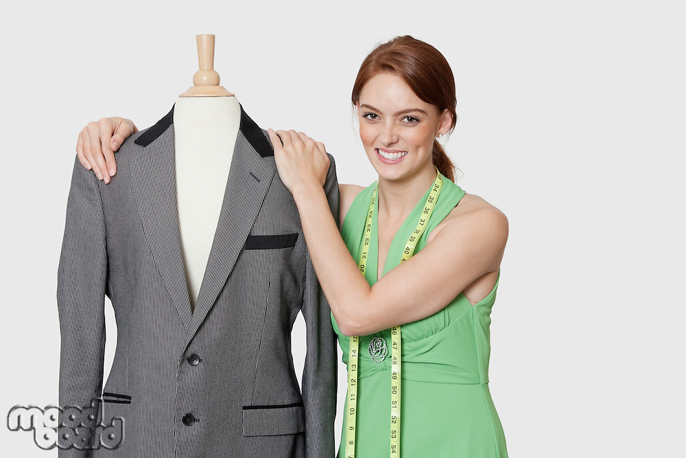 Portrait of beautiful female dressmaker standing with tailor's dummy over gray background