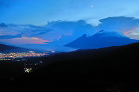 Aerial drone image of Volcán de Fuego and Volcán de Acatenango (left and right peaks in the distance) at sunset, seen from above Antigua Guatemala, on Tuesday, Sept. 18, 2018. While Acatenango is dormant, Fuego is highly active and an eruption on June 3, 2018 caused heavy loss of life and property.