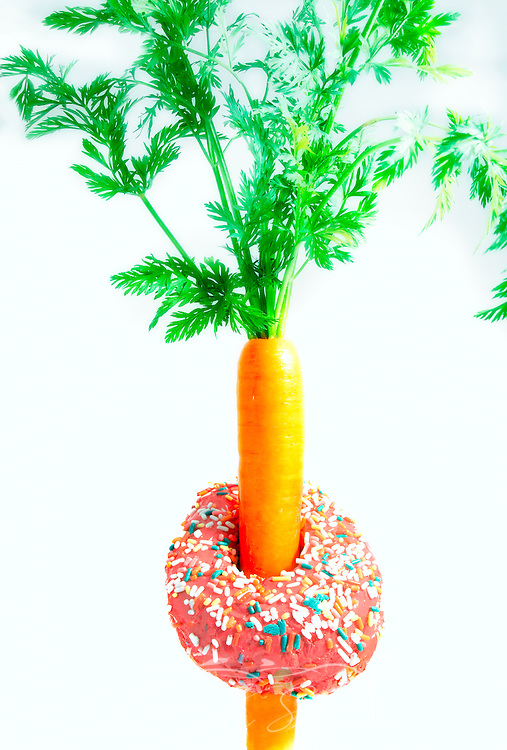 "A pink frosted doughnut encircles the ""waist"" of a fresh carrot, March 30, 2016, in Coden, Alabama. One medium carrot has approximately 25 calories. A typical frosted doughnut has more than 250 calories. (Photo by Carmen K. Sisson/Cloudybright)"