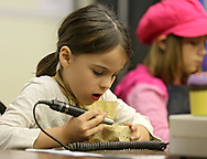Alyse Burns, 5, of Marion hard at work on a carving of a dog during a meeting of the Cedar Valley Woodcarvers in Midway on Saturday, May 25, 2013.
