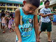 29 JANUARY 2018 - GUINOBATAN, ALBAY, PHILIPPINES: Children play games during an activity hour at the shelter for evacuees from Mayon volcano in Mauraro National High School in Guinobatan. There are 1,773 people in the shelter. Mayon volcano's eruptions continued Monday. At last count, more 80,000 people have been evacuated from their homes of the slopes of the volcano and are crowded into shelters in communities outside of the danger zone.    PHOTO BY JACK KURTZ