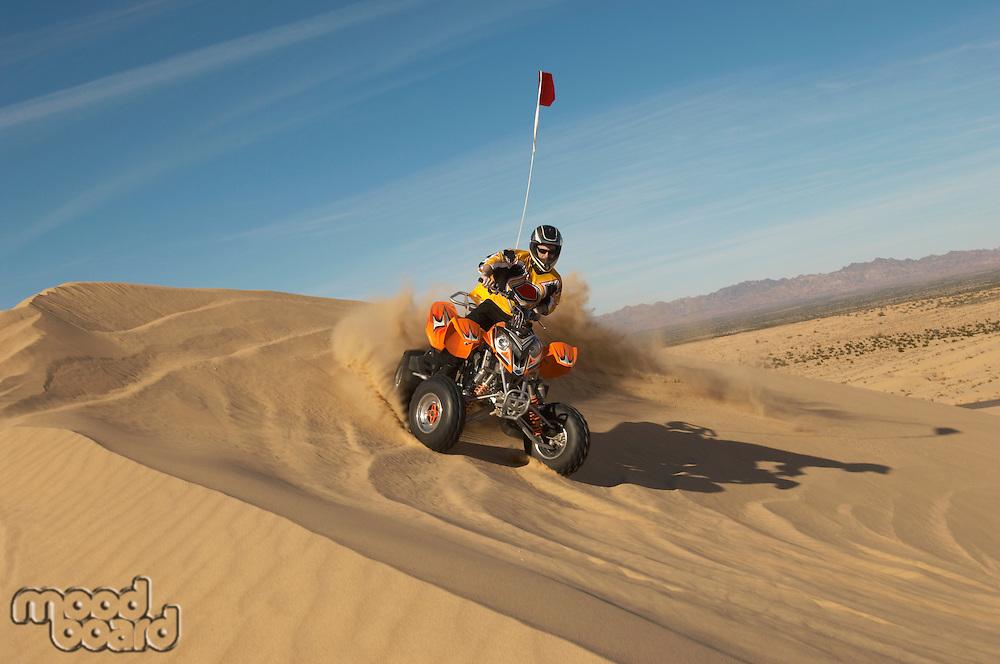 Man riding quad bike in desert