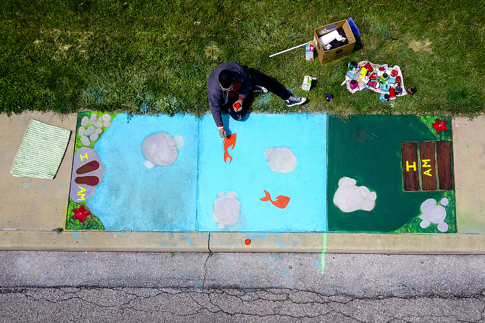 Local artist Sharron High of York creates a sidewalk mural near Hannah Penn K-8 for the Playful Sidewalk Initiative, Sunday, May 7, 2017. High's theme was a pond with stepping stones that has positive word for positive affirmations.  John A. Pavoncello photo