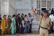Visitors overlooked by Indian police officers are making their way to the Taj Mahal building and tombs, in Agra.