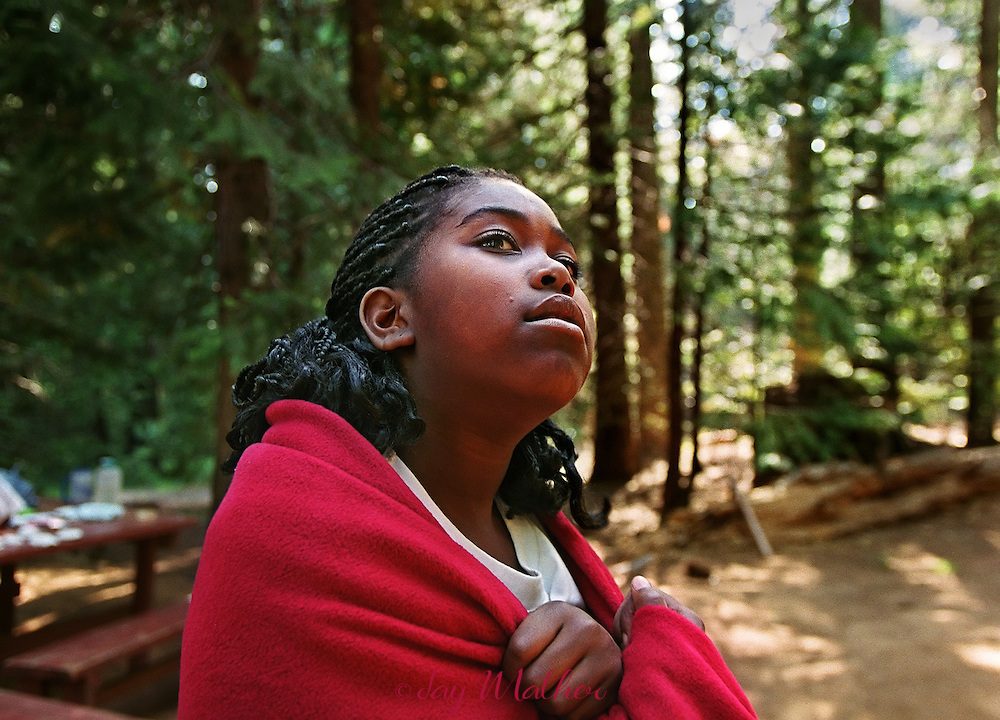 "Aaliyah Fowler (cq), 10, from Sacramento, ponders the nature surrounding her on a cool afternoon at Camp Menzies Girl Scout camp.  She was noticing the new growth on the pine trees near her tent Each afternoon the girls have ""me"" time when they read, write letters home or just be quiet with their thoughts.  June 28, 2000.  ...The Sacramento Bee"