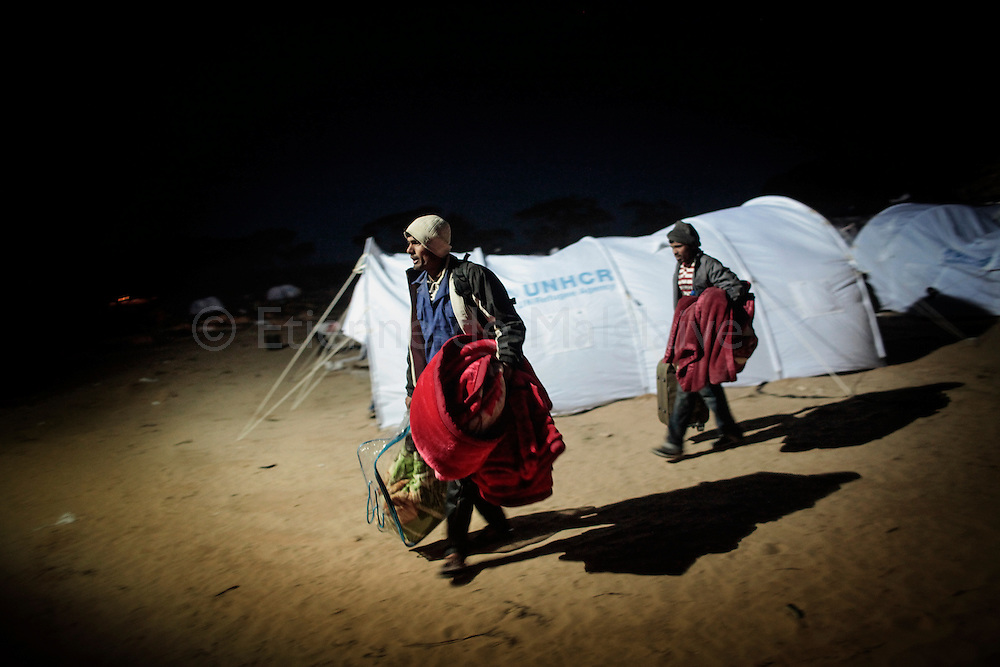 After crossing  border from Libya, migrants workers arrive in an UNHCR transit camp in Choucha, walking 7 km from Tunisia's Ras Jdir border station. They will be hold in this camp waiting for repatriation to their home countries.<br /> 03 March 2011.