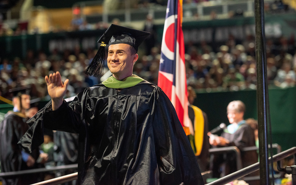 J.R. Cramer waves to supporters during graduate commencement. Photo by Ben Siegel