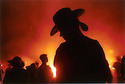A woman basks in the glow of the fire on the last night of the Burning Man Festival in Black Rock Desert in Nevada.  On the last night of the one week festival the temporary community burns the symbolic man and the temporary village. 9/1/2001