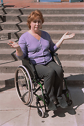 Female wheelchair user in front of steps protesting about lack of access,