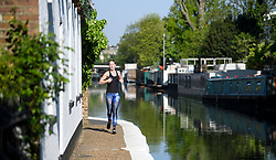 © Licensed to London News Pictures. 06/05/2018. London, UK. A jogger along the towpath at Day two of the Canalway Cavalcade festival takes place in Little Venice, West London on Sunday,  May 6th 2018. Inland Waterways Association's annual gathering of canal boats brings around 130 decorated boats together in Little Venice's canals on May bank holiday weekend. Photo credit: Ben Cawthra/LNP