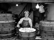 A woman sells steamed bread in an old Shanghai neighborhood.