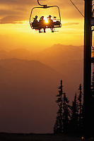 Three people ride the chairlift into the sunset, Blackcomb Mountain, Whistler, BC