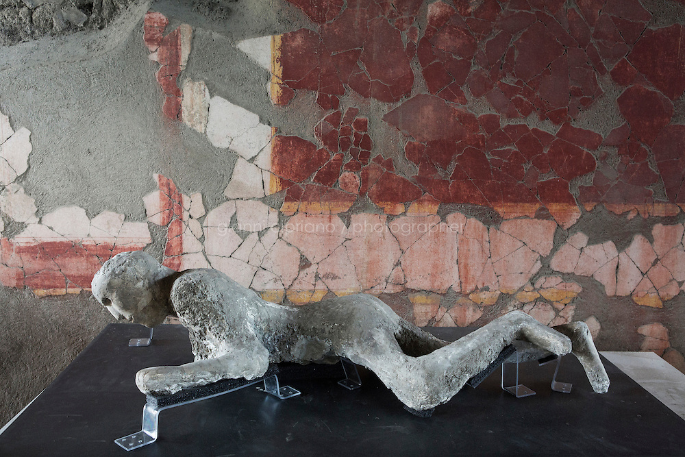 POMPEII, ITALY - 29 SEPTEMBER 2015: The cast of a victim of the 79 AD Mount Vesuvius eruption is here in the Pompeii Casts Restoration Site in the archeological site of Pompeii, Italy, on September 29th 2015.<br /> <br /> Pompeii, along with Herculaneum, was buried under 4 to 6 meters (13 to 20 ft) of ash and pumice in the eruption of Mount Vesuvius in 79 AD. After its initial discovery in 1599, Pompeii was rediscovered as the result of intentional excavations in 1748 by the Spanish military engineer Rocque Joaquin de Alcubierre.<br /> <br /> Pompeii is an UNESCO World Heritage Site and one of the most popular tourist attractions of Italy, with approximately 2.5 million visitors every year.