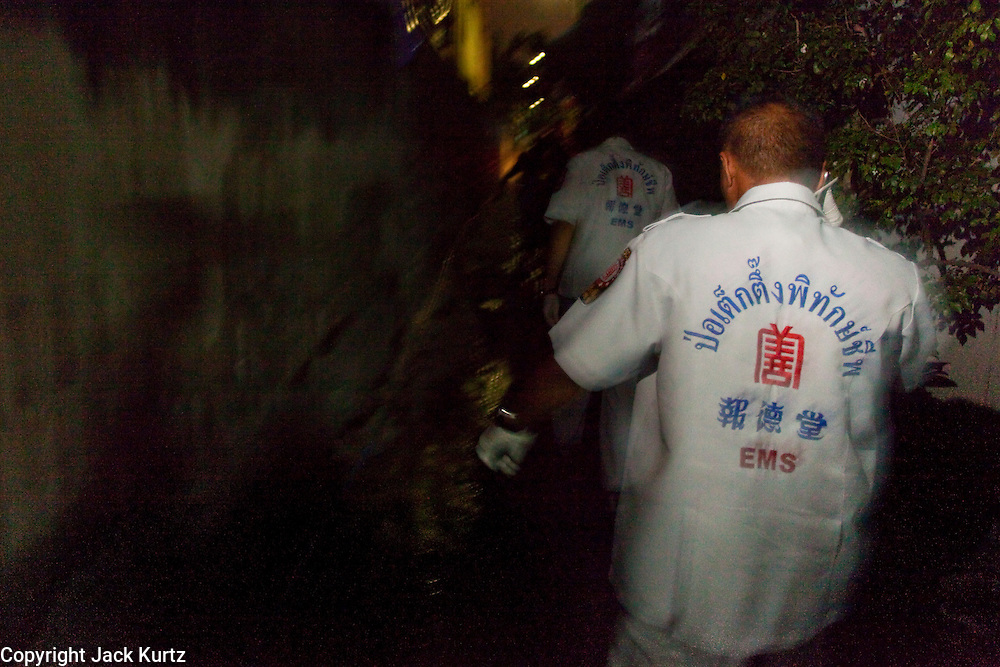 "Oct. 1, 2009 -- BANGKOK, THAILAND:  Medics from Poh Teck Tung run through a narrow alley in Bangkok rushing to the home of a woman who attempted suicide. The 1,000 plus volunteers of the Poh Teck Tung Foundation are really Bangkok's first responders. Famous because they pick up the dead bodies after murders, traffic accidents, suicides and other unplanned, often violent deaths, they really do much more. Their medics respond to medical emergencies, from minor bumps and scrapes to major trauma. Their technicians respond to building collapses and traffic accidents with heavy equipment and the ""Jaws of Life"" and their divers respond to accidents in the rivers and khlongs of Bangkok. The organization was founded by Chinese immigrants in Bangkok in 1909. Their efforts include a hospital, college tuition for the poor and tsunami relief.    Photo by Jack Kurtz / ZUMA Press"
