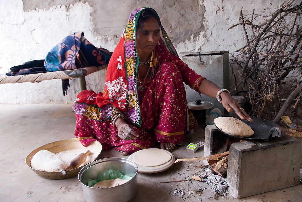 A mother from Rajasthan (Thar desert, India) prepares chapati, a staple flat bread made from unleavened cooked dough (type of roti). The dough, water and salt are rolled out and browned on both sides on a very hot frying pan. Very often, chapatis are eaten with dal (lentil soup) or vegetable dishes.