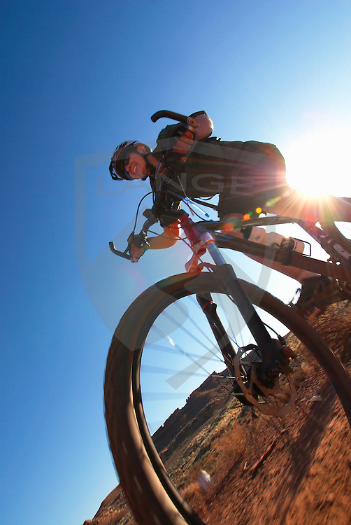 outdoor sports, recreation, travel, and adventure: smiling woman mountain biking with sun (sunshine lens flare), white rim trail, canyonlands national park, utah, vertical, wide angle, low angle, copy space