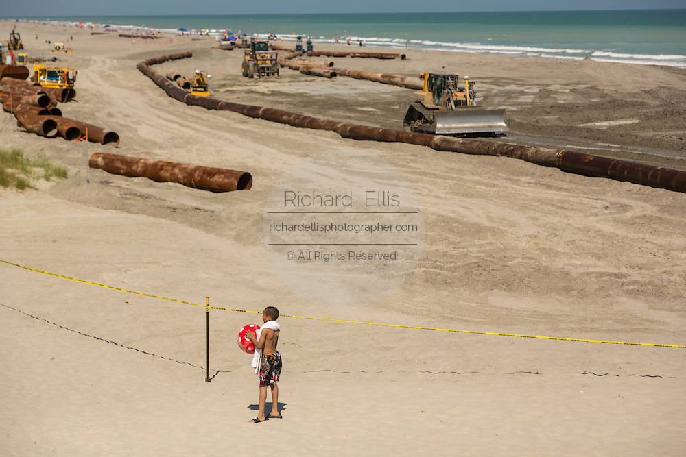 A small boy watches the Army Corps of Engineers use heavy machinery to restore the beach during a major beach replenishment project May 12, 2014 in Folly Beach, SC.