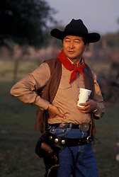 cowboy standing outside with a drink