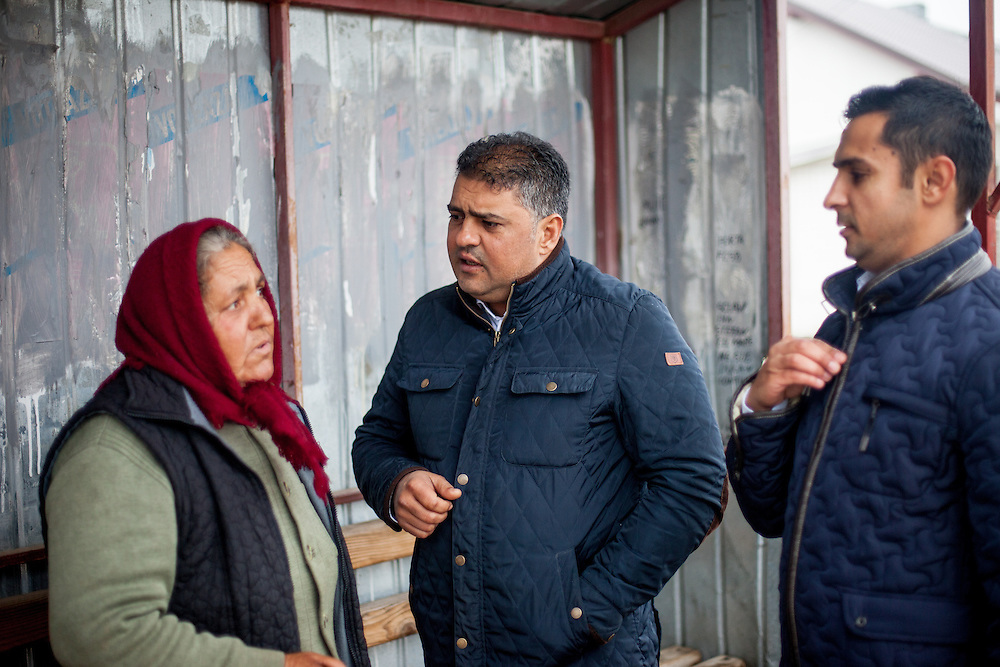 Roma activists Marius Tudor (right) and Marian Daragiuin (left) discussing with  Niculina, a Roma woman waiting for her bus about the upcoming presidential elections in Romania.