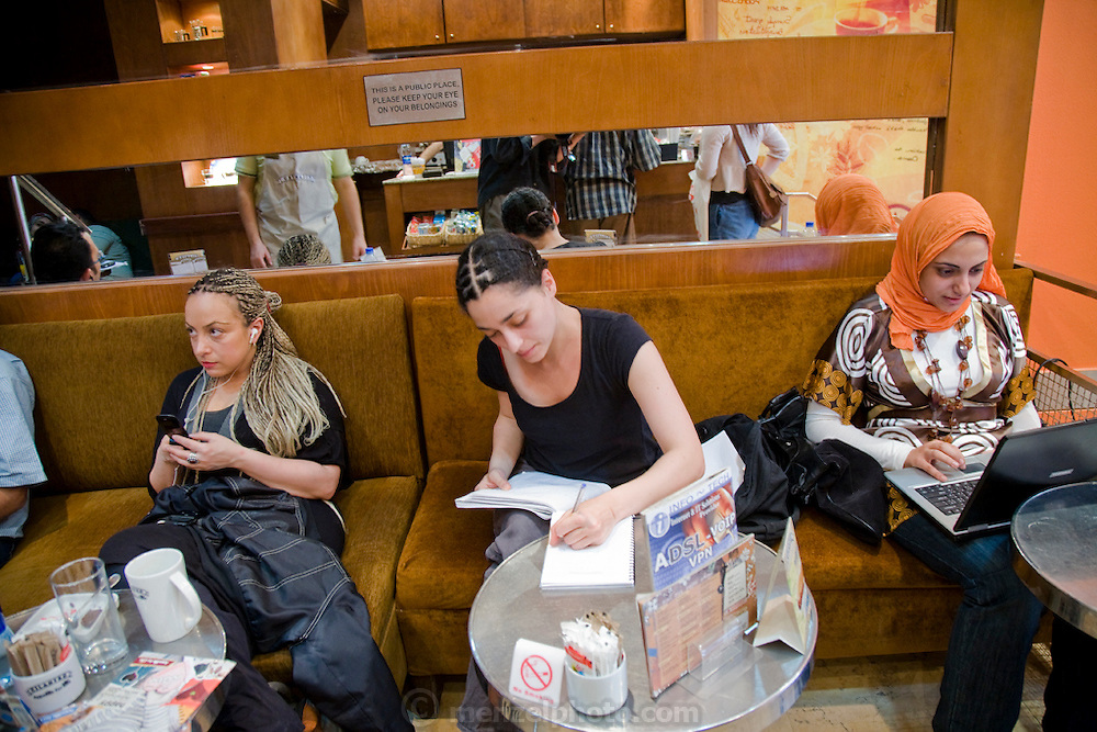 Customers use their laptops for email and talk on cellphones at Cilantro, a coffee and internet shop in Cairo, Egypt.
