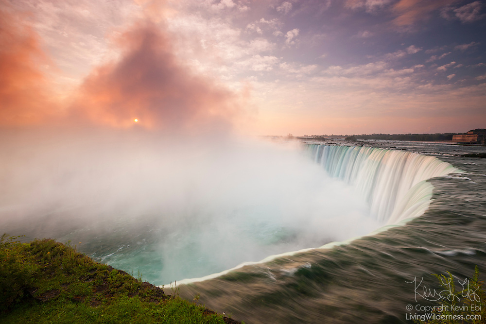 The rising sun shines through the thick mist generated by the force of Horseshoe Falls, one of the waterfalls that make up Niagara Falls on the border of New York and Ontario. About 90 percent of the water in the Niagara River flows over Horseshoe Falls, which amounts to about 600,000 gallons (2.3 million liters) of water per second. The waterfall is about a half-mile wide, with a brink length of 2600 feet (792 meters), and it is 167 feet (51 meters) high. Horseshoe Falls is also known as Canadian Falls, since about two-thirds of it is located in Canada. It is pictured here from the Canadian side.
