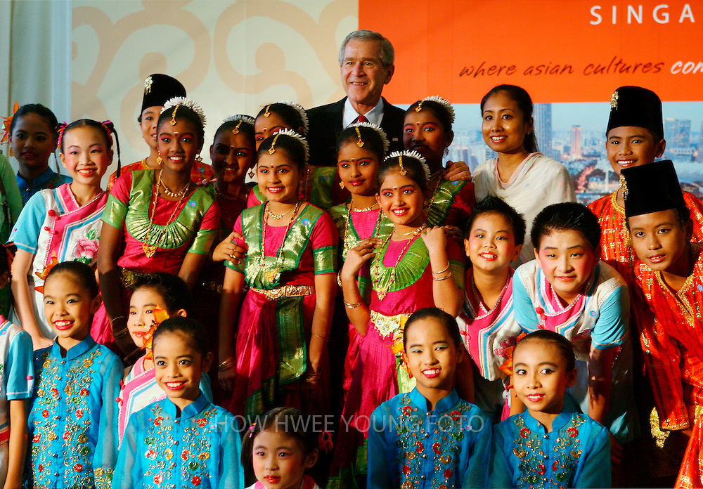 epa00863560 U.S. President George W. Bush (back C) pose for a group photo with students after they perform a Chinese, Malay and Indian ethnic dance medley for him during a tour of the Asian Civilisation Museum in Singapore on Thursday 16 November 2006. Bush arrives in Singapore Thursday while enroute to attend the annual Asia-Pacific Economic Cooperation (APEC) summit in Vietnam.  EPA/HOW HWEE YOUNG