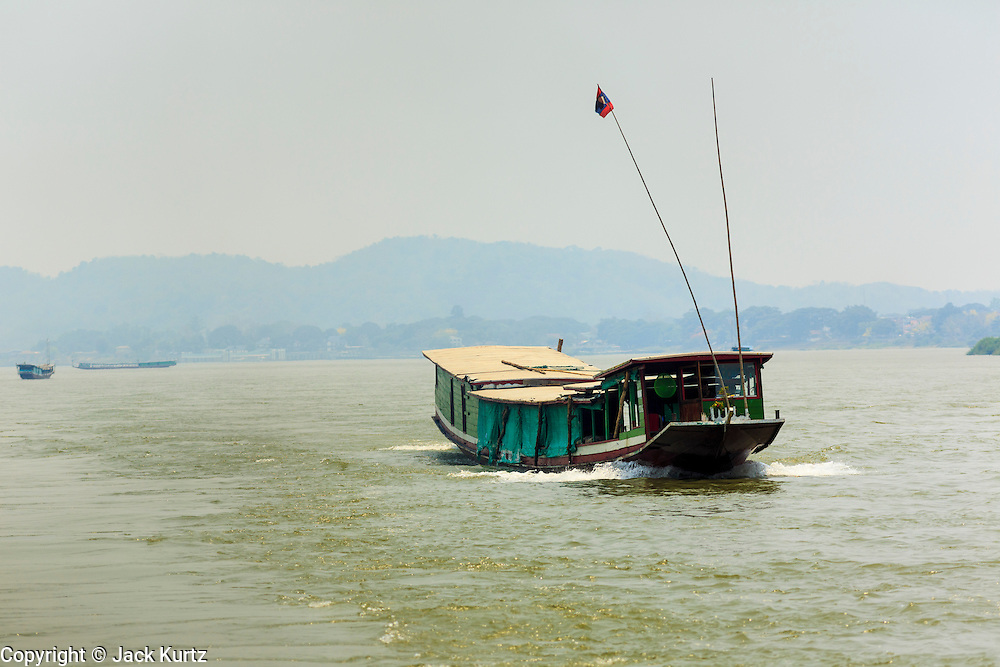 24 APRIL 2014 - CHIANG SAEN, CHIANG RAI, THAILAND:  A Lao flagged river boat cruises north on the Mekong River. Chinese businesses play an increasingly important role in the Chiang Rai economy. Consumer goods made in China are shipped to Thailand while agricultural products made in Thailand are shipped to China. Large Chinese cargo boats ply the Mekong River as far south as Chiang Saen in the dry season and Chiang Khong when river levels go up in the rainy season.    PHOTO BY JACK KURTZ