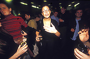 A female drinker approaching the camera while surrounding people hold glasses of wine, UK 2000's