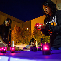 102713  Adron Gardner/Independent<br /> <br /> Amber Armstrong, right, blows out a flame as Al-Gerradson Nez, left, and Faye Gillespie, center, collect candles after a domestic violence candlelight vigil at the McKinley County Courthouse in Gallup Sunday.