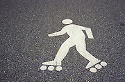 white painted figure of roller skater on asphalt