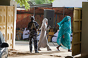 Under the watchful eye of a Sudanese policeman armed with an Kalashikov AK-47, lady delegates attending the first-ever international Conference on Womens' Challenge in Darfur, walks near the gate of the compound belonging to the Govenor of North Darfur in Al Fasher (also spelled, Al-Fashir) where the women from remote parts of Sudan gathered to discuss peace and political issues.