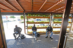 JOHANNESBURG SOUTH AFRICA - MAY 01 Delivery drivers wait as Hudsons Parkhurst staff prepare food for delivery on May 01, 2020 in Johannesburg South Africa. South Africa moved down to Level 4 of the national lockdown with relaxed restrictions as part of a risk adjusted 5 stage phasing of lockdown measures. This includes allowing of certain restaurants to reopen for trade and prepare hot food as delivered takeaway only. (Photo by Gallo Images/ Dino Lloyd)
