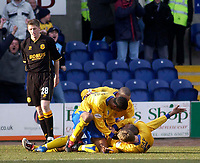 Photo. Glyn Thomas.<br /> Mansfield Town v Hull City.<br /> Nationwide League Division 3.<br /> Field Mill, Mansfield. 06/03/2004.<br /> Mansfield Town's Laurent D'Jeffo is mobbed by teammates after scoring the winning goal as Hull's Richard Hinds (L) can only look on in disbelief.