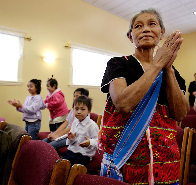 Karen refugee Nwee Leh prays while attending a Sunday morning service at Living Faith Christian Church in Waterbury. More than 60 refugees have been relocated to Waterbury since late summer.   .(Photo by Robert Falcetti)