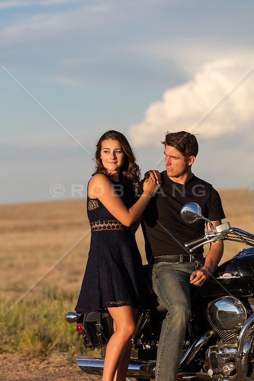 sexy couple taking a break on a motorcycle at sunset