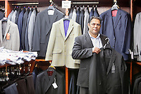 Portrait of man shopping for formal coat in menswear store