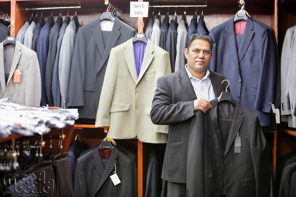 Portrait of man shopping for formal coat in menswear store