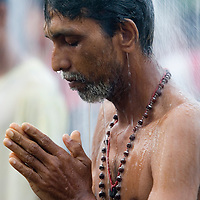 "Hindu devotee takes a shower before their pilgrimage to the sacred Batu Caves temple during the Thaipusam festival in Kuala Lumpur, Malaysia. Hindu devotees celebrate Thaipusam festival in honour of the Lord Murugan (also known as Lord Subramaniam). Thousands of Hindu devotees carried the milk pots and ""kavadi"" (a gaily decorated wooden or metal frame) walk barefoot up the temple's 272 steps to undergo penance in fulfilling vows made to Lord Murugan for answering their prayers."