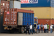 Men stand near a truck carrying a container at the sea port in Lome, Togo on Friday October 3, 2008.