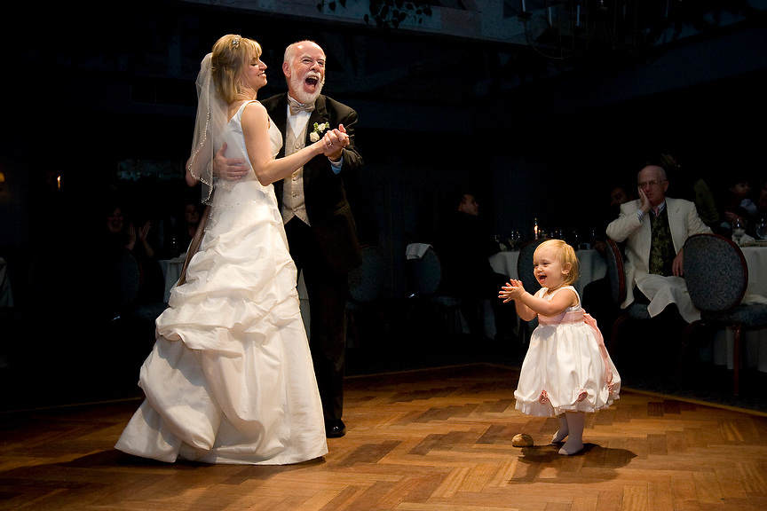 (Scituate, MA - November 9, 2008) -  Jan Hutton and her father John laugh as her daughter Eva tries to join in on the dance floor during the reception at Barker's Tavern in Scituate...This photo placed 9th in the Dancing category of the 2009 WPJA/Brides Magazine Photo Contest. ..Photo by Will Nunnally / Will Nunnally Photography