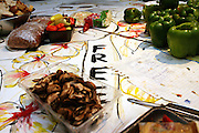 Table covered with various items at a Freegan dinner made entirely with food recovered from dumping sites around the island of Manhattan, New York, NY., on Friday, June 23, 2006. Freegans are a community of people who aims at recovering wasted food, books, clothing, office supplies and other items from the refuse of retail stores, frequently discarded in brand new condition. They recover goods not for profit, but to serve their own immediate needs and to share freely with others. According to a study by a USDA-commissioned study by Dr. Timothy Jones at the University of Arizona, half of all food in the United States is wasted at a cost of $100 billion dollars every year. Yet 4.4 million people in the United States alone are classified by the USDA as hungry. Global estimates place the annual rate of starvation deaths at well over 8 million. The massive waste generated in the process fills landfills and consumes land as new landfills are built. This waste stream also pollutes the environment, damages public health as landfills chemicals leak into the ground, and incinerators spew heavy metals back into the atmosphere. Freegans practice strategies for everyday living based on sharing resources, minimizing the detrimental impact of our consumption, and reducing and recovering waste and independence from the profit-driven economy. They are dismayed by the social and ecological costs of an economic model where only profit is valued, at the expense of the environment. In a society that worships competition and self-interest, Freegans advocate living ethical, free, and happy lives centred around community and the notion that a healthy society must function on interdependence. Freegans also believe that people have a right and responsibility to take back control of their time.