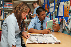 Pupils in school library looking at books and newspapers.