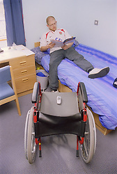Young man; who is a wheelchair user; lying on bed reading magazine in purposebuilt bedsit at direct access hostel for homeless and vulnerably housed young people,