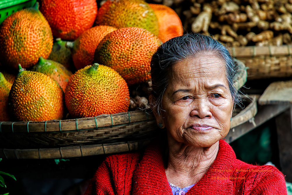 Morning Fruit: In the morning market a woman takes a moment for herself, as she rests, her head adjacent to a basket of fruit, Hue Vietnam.