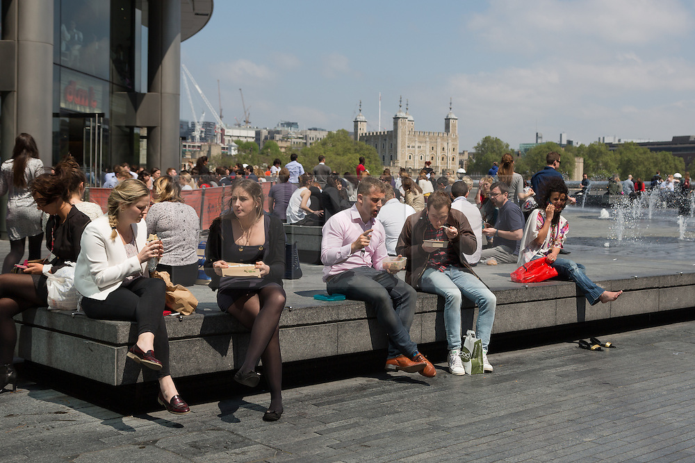 © Licensed to London News Pictures. 13/06/2016. LONDON, UK.  Office workers enjoying the sunny spring weather at lunchtime on the south bank in front of the Tower of London.  Photo credit: Vickie Flores/LNP