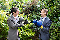 Two young men in suits stage a mock boxing match