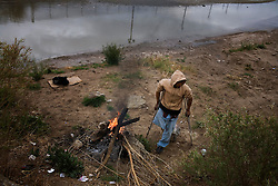 A homeless drug addict builds a fire to stay warm near the Rio Grande river that separates El Paso, Texas and Ciudad Juarez, Mexico.  Mexico is undergoing a violent war with the nation's drug cartels and Ciudad Juarez has become the murder capital of Mexico, with over 4,000 murders in the past two years.  President Felipe Calderon has dispatched thousands of soldiers and federal police officers in order to contain the situation, but they have not been successful.