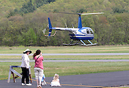 Wurtsboro, NY - A woman takes a picture of  Robinson R44 helicopter taking off from  Wurtsboro Airport on May 11, 2008.