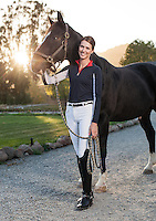 Dressage rider and trainer Riana Porter (MR) standing with horse on gravel drive with sunset in background.