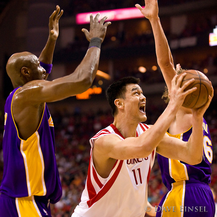 Houston Rockets' Yao Ming of China (C) drives between Los Angeles Lakers' Lamar Odom (L) and Pau Gasol of Spain (R) during the first quarter of their NBA Western Conference Semifinal Playoff game at the Toyota Center in Houston, Texas, USA, 8 May 2009.